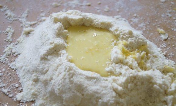 В отдельной чаше смешать муку, соль и сахар. Высыпать на разделочную доску и добавить мягкое, но не растаявшее масло. Перетереть муку и масло между руками в крошку. Сделать з получившейся смеси горку, а в ней углубление.